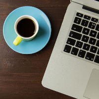 Coffee cup on a saucer with a laptop on a wooden table
