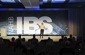 Woman in white shirt and dark pants stands in front of NAHB/IBS logo on blue background